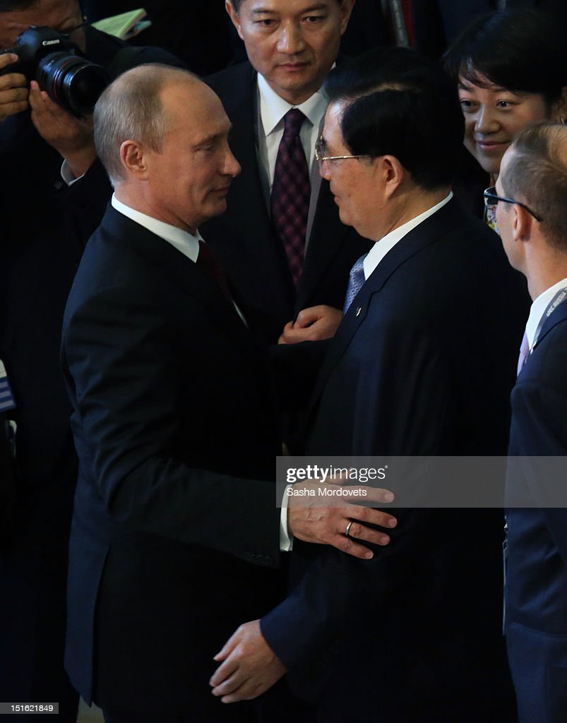 Russian President Vladimir Putin (L) greets Chinese President Hu Jintao (R) during a session of the Asian Pacific Economic Cooperation (APEC) Summit September 9, 2012 in Vladivostok, Russia. Leaders of APEC countries are gathered at Russky Island in Vladivostok to seek freer trade among member nations.