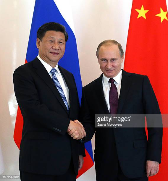 Russian President Vladimir Putin greets Chinese President Xi Jinping during the BRICS leaders meeting prior to G20 Antalya Summit in Belek near...