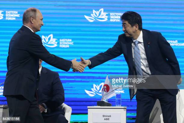 Russian President Vladimir Putin greets Japanese Prime Minister Shinzo Abe at the plenary session of the Eastern Economic Forum on September 7 2017...