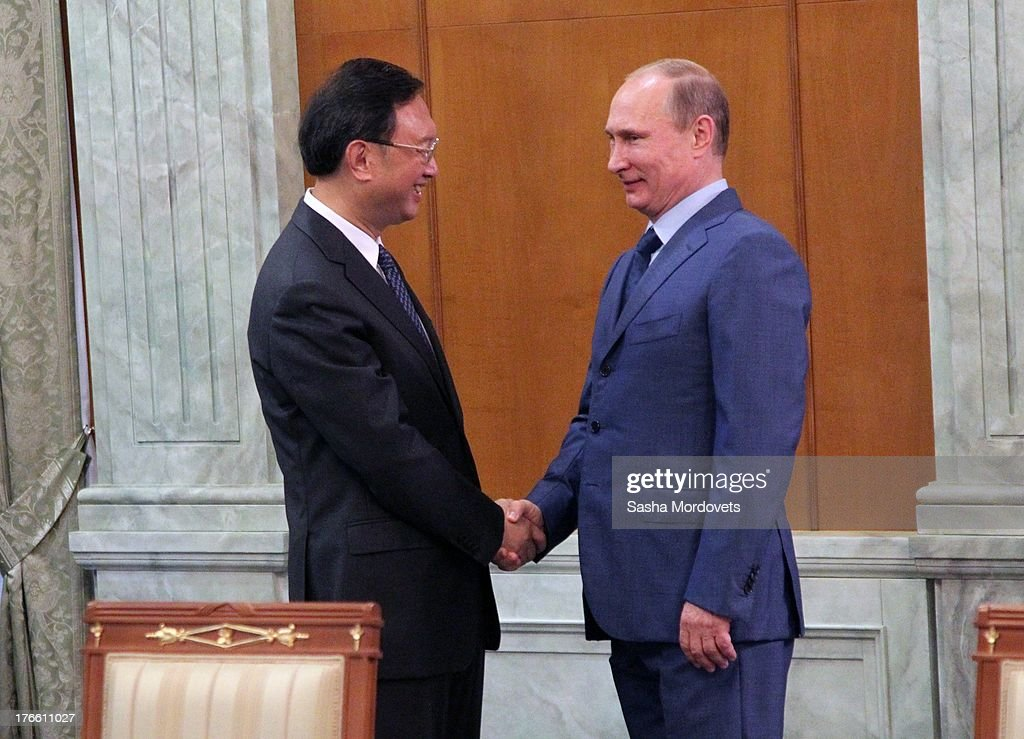 Russian President Vladimir Putin (R) greets member of China's State Council Jang Jiechi (L) on August 16, 2013 in Sochi, Russia. Jeichi has arrived to Putin's Black Sea resort residence for negotiations.