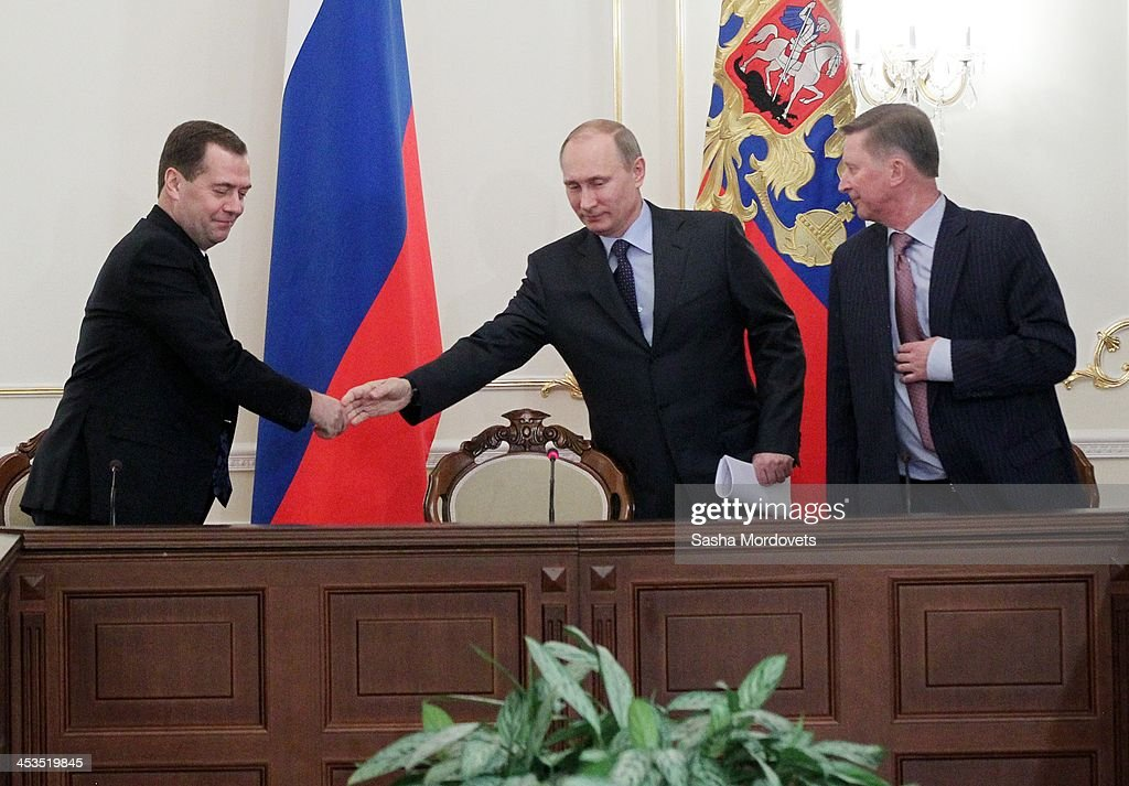 Russian President Vladimir Putin greets Prime Minister Dmitry Medvedev as Head of the Presidential Administration Sergei Ivanov looks on during the...
