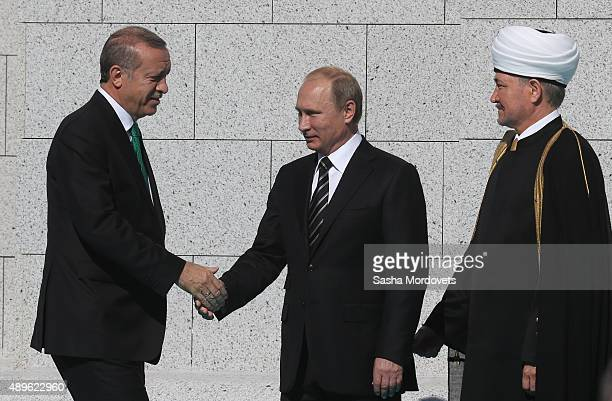 Russian President Vladimir Putin greets Turkish President Tayyip Erdogan and Russian Grand Mufti Ravil Gainutdin during an opening ceremony for the...