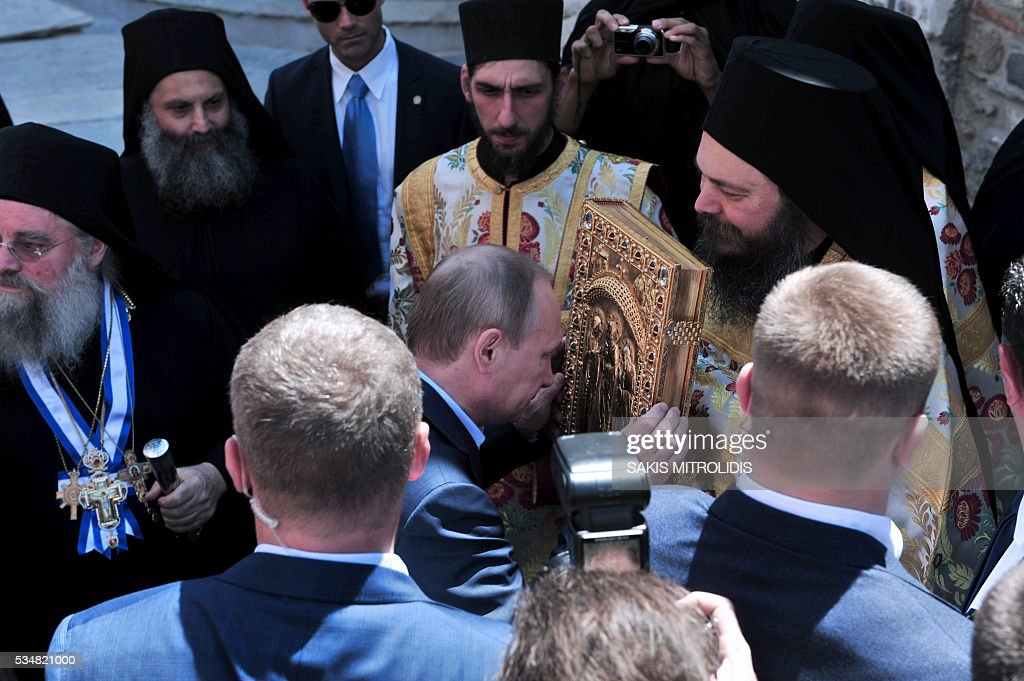 Russian President Vladimir Putin (C) holds a book during a visit to the monastic community of Mount Athos, in Karyes on May 28, 2016. Putin, who has often talked about his strong Orthodox faith, will join celebrations for the 1,000th anniversary of the Russian presence at the ancient, all-male monastic community of Mount Athos. The visit, Putin's first to the EU since December, comes at a low ebb in relations between Russia and Europe over the conflict in Ukraine that broke out in 2014, with sanctions still in force against Moscow. / AFP / SAKIS