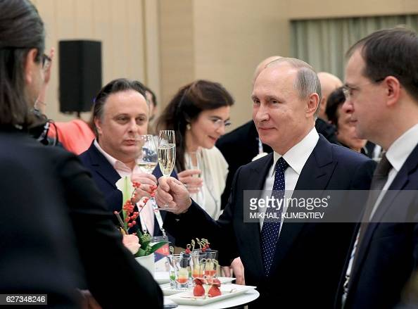 Russian President Vladimir Putin holds a glass of champagne during a ceremony at the Mariinsky Theatre as part of his visit to Saint Petersburg on...