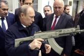 Russian President Vladimir Putin holds a Kalashnikov machine gun during his visit to the Kalashnikov manufacturing plant September 18 2013 in Izhevsk...
