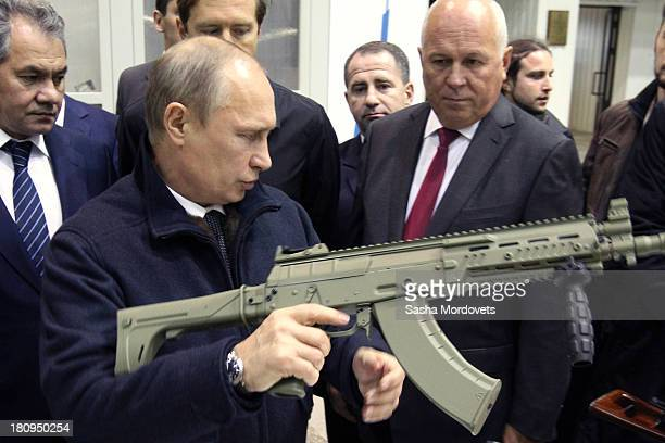 Russian President Vladimir Putin holds a Kalashnikov machine gun during his visit to the Kalashnikov manufacturing plant September 18 2013 in Izhevsk...