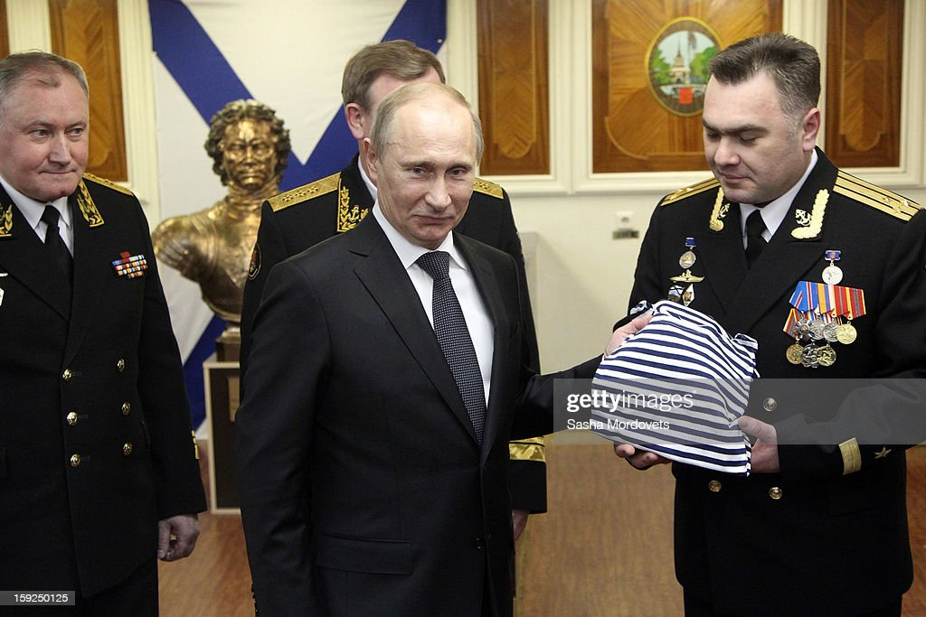 Russian President Vladimir Putin (C) holds a sailor's striped vest during his visit to the heavy nuclear-powered missile cruiser Pyotr Veliky at the Russian Northern Fleet's base January 10, 2013 in Severomorsk, Russia. Putin awarded the crew of the Pyotr Veliky the Nakhimov order.