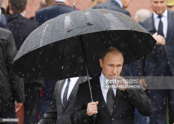 TOPSHOT Russian President Vladimir Putin holds an umbrella as he attends a ceremony marking the 76th anniversary of the Nazi German invasion by the...