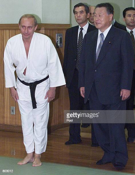 Russian President Vladimir Putin in judo gear escorted by Japanese Prime Minister Yoshiro Mori right bows before entering Kodokan judo hall in Tokyo...