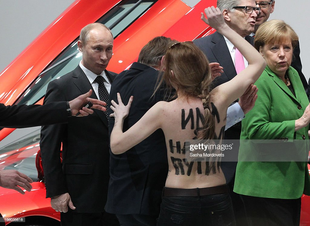 Russian President Vladimir Putin (L) is attacked by an activist of the Ukrainian women rights group 'Femen' as German Chancellor Angela Merkel (R) looks on during their visit of the industrial exhibition 'Hannover Messe' on April 8, 2013 in Hannover, Germany. More than 100 Russian companies are exhibiting their industrial productions.