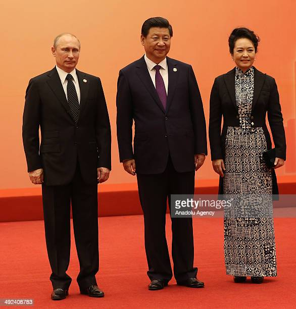 Russian President Vladimir Putin is greeted by Chinese President Xi Jinping and his wife Peng Liyuan before a group photo at the fourth Conference on...
