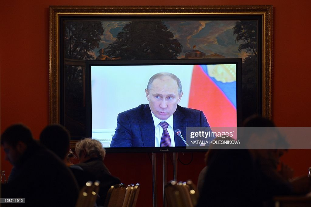 Russian President Vladimir Putin is seen on a TV set screen as he speaks during a State Council meeting at the Kremlin, in Moscow, on December 27, 2012. Putin told today a meeting of top officials in the Kremlin he intended to sign into law a bill banning Americans from adopting Russian children that has raised tensions between Moscow and Washington. AFP PHOTO / POOL/ NATALIA KOLESNIKOVA