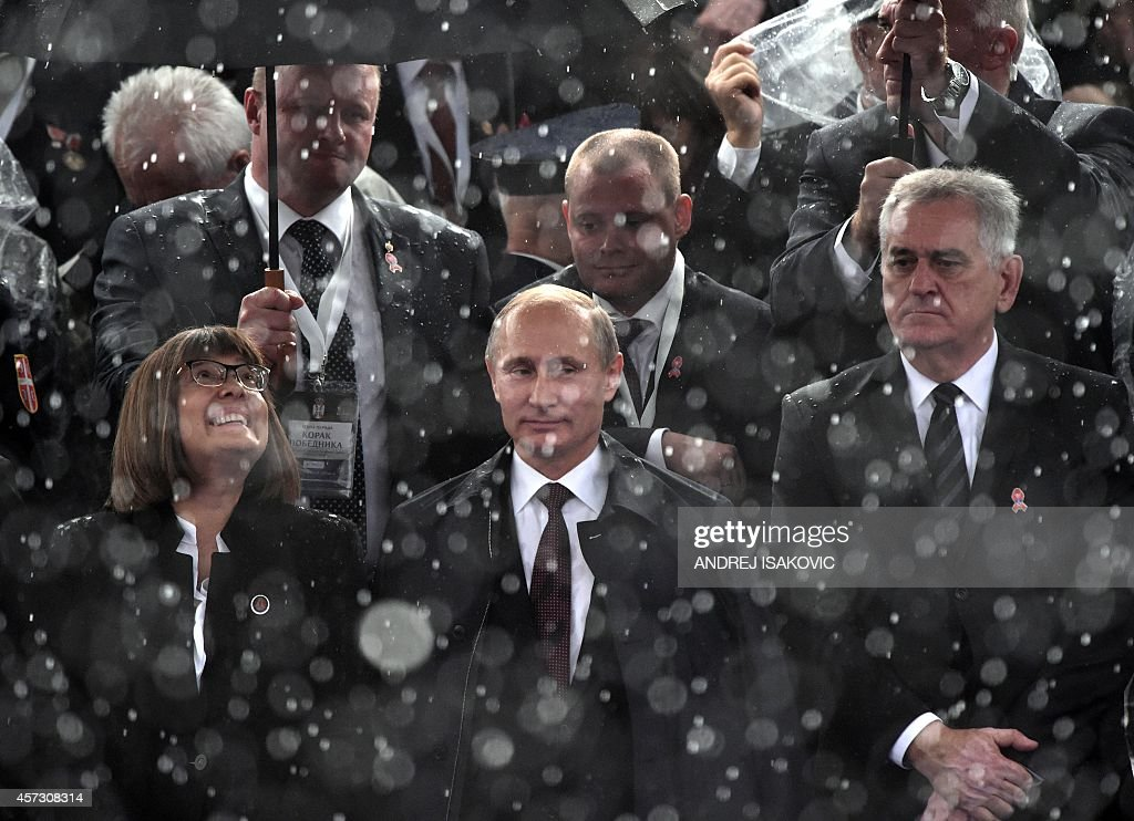 Russian President Vladimir Putin is seen trough a heavy rainfall during a military parade in Belgrade on October 16 2014 Putin was expected to secure...