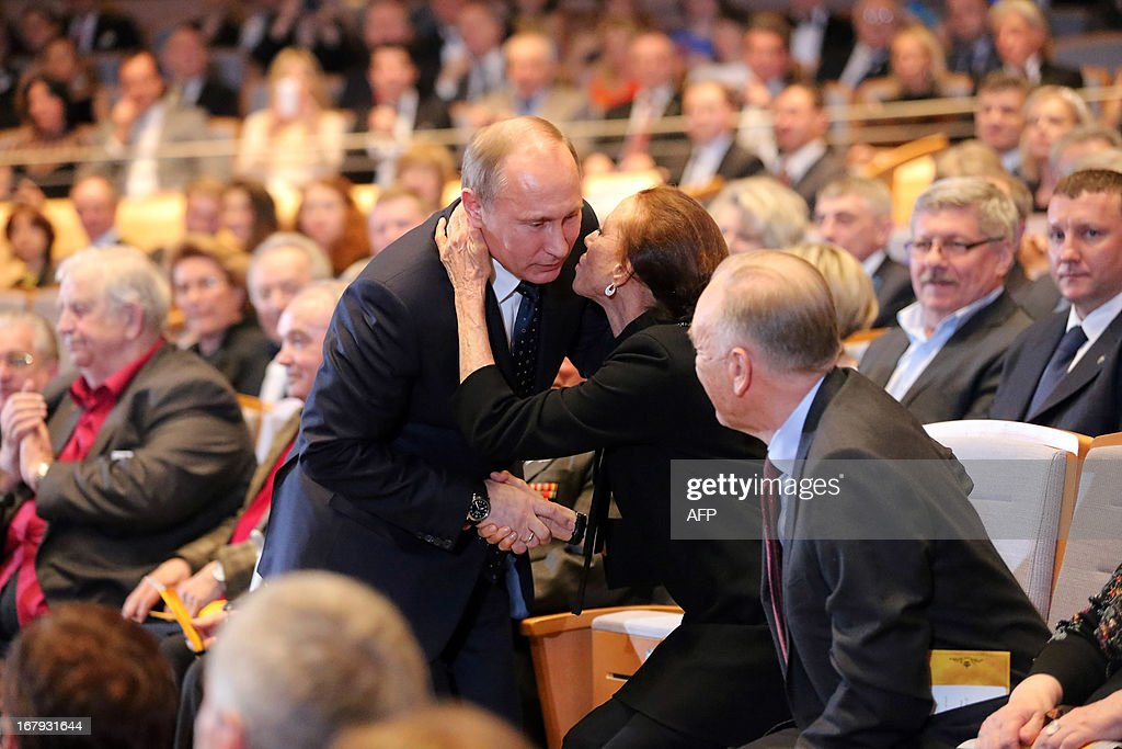 Russian President Vladimir Putin (L) kisses famous ballerina Maya Plisetskaya (C) during the Grand gala dedicated to the opening of the new stage Mariinsky II theatre in St. Petersburg, on May 2, 2013. Russia's famous Mariinsky theatre in Saint Petersburg was to inaugurate a new ballet and opera house on May 2 in an event coinciding with the 60th birthday of its hugely ambitious and well-connected director Valery Gergiev.