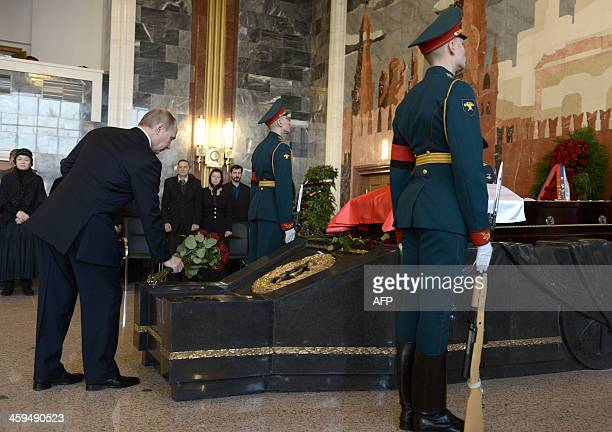 Russian President Vladimir Putin lays flowers as he pays his last respects to Mikhail Kalashnikov the designer of the iconic AK47 assault rifle that...