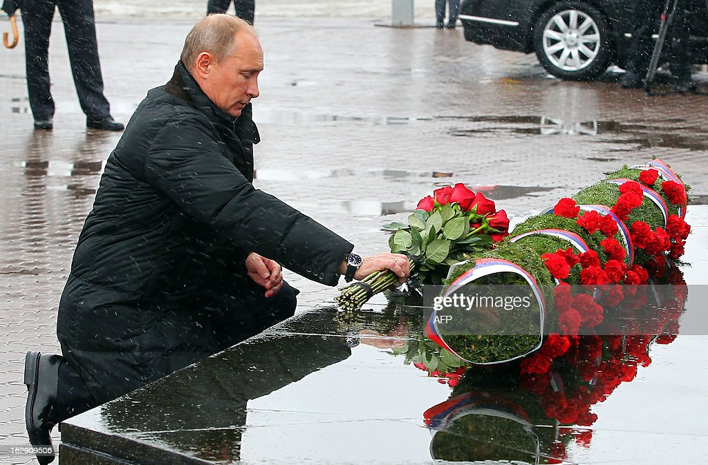 Russian President Vladimir Putin lays flowers at the memorial of the fallen servicemen as he visits the 104th Guard Air Assault Regiment of the 76th Guard Air Assault Division in Pskov on March 1, 2013.