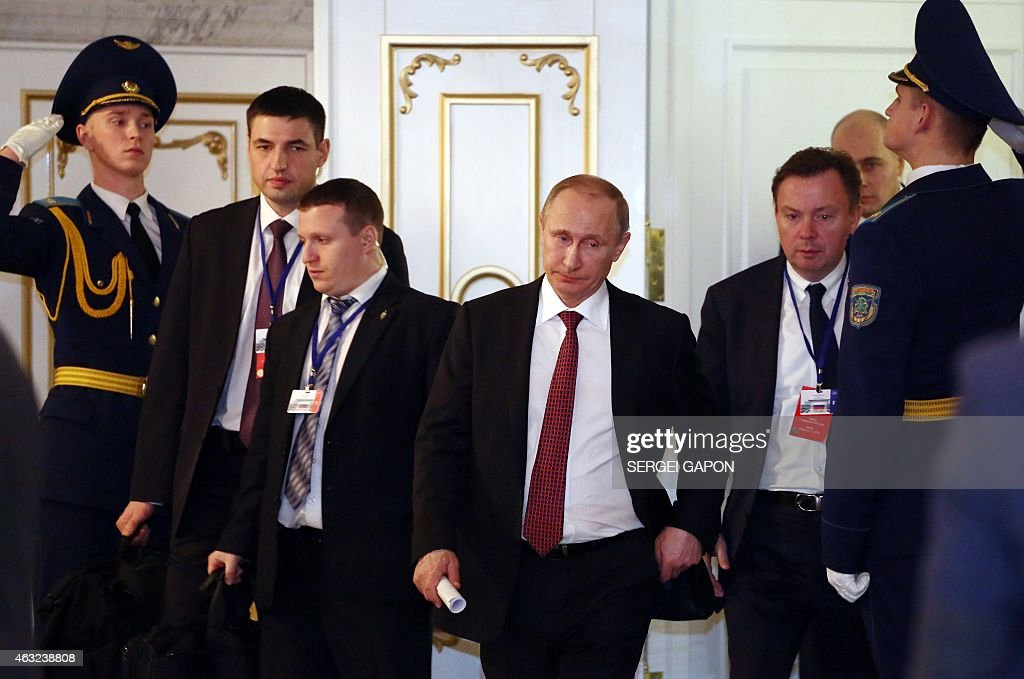 Russian President Vladimir Putin leaves a hall at the presidential residence in Minsk on February 12 during a meeting aimed at ending 10 months of...