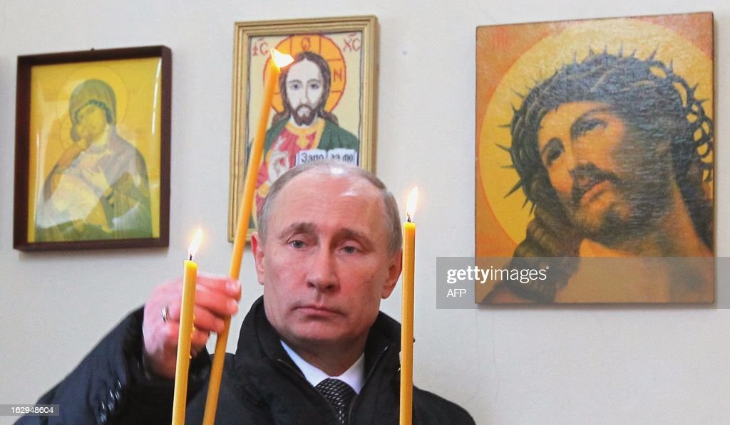 Russian President Vladimir Putin lights a candle at a church as he visits the 104th Guard Air Assault Regiment of the 76th Guard Air Assault Division in Pskov, northeastern Russia, on March 1, 2013.