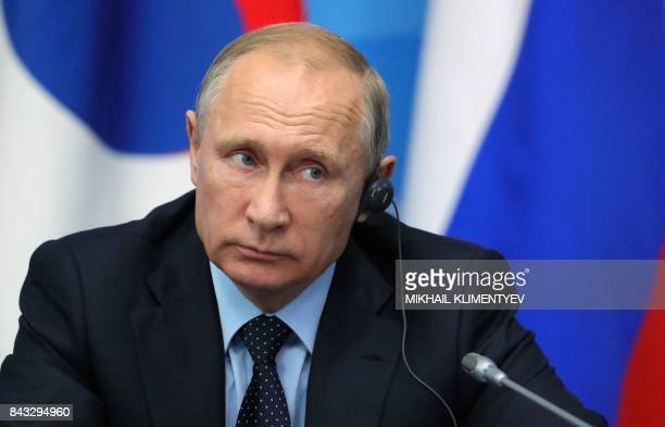 Russian President Vladimir Putin listens as he attends a joint press statement with President of South Korea after their meeting held at the 3rd...