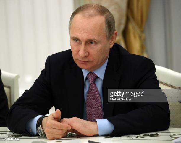 Russian President Vladimir Putin listens during a meeting with Director of the General Office of the Communist Party of China and Chief of the...