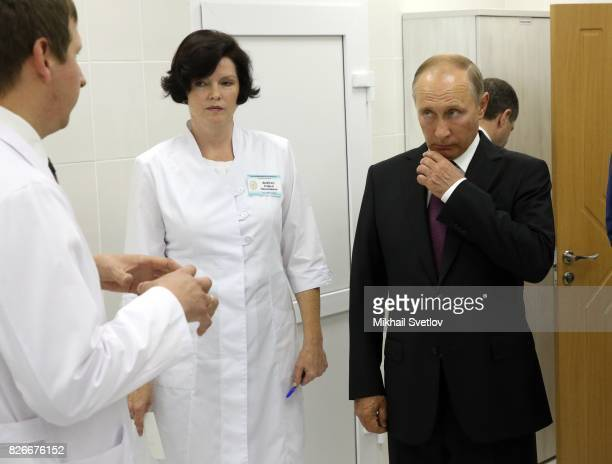 Russian President Vladimir Putin listens to a doctor while visiting the Medical Clinical and Dignostic Center on August 5 2017 in Kirov Russia...