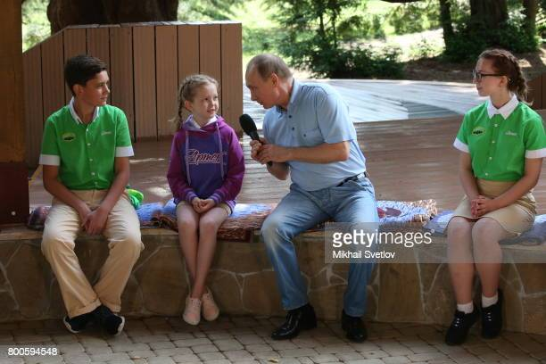 Russian President Vladimir Putin listens to a girl during his meeting at Artek camp an international children center on the Black Sea on June 24 2017...