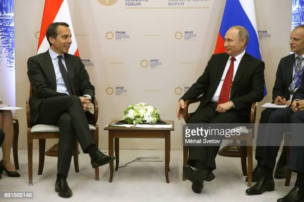 Russian President Vladimir Putin listens to Austrian Chancellor Christian Kern during their meeting at the Saint Petersburg International Economic...