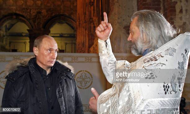 Russian President Vladimir Putin listens to Father Nikita after an Orthodox Christmas service at a church in New Jerusalem a 17thcentury monastery...