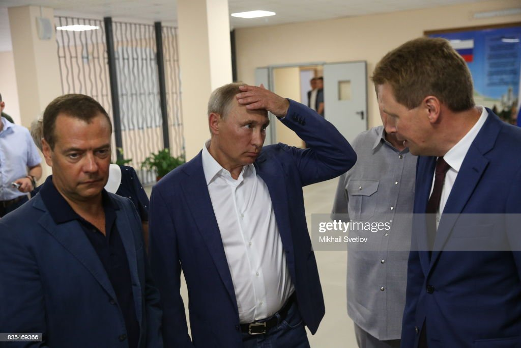Russian President Vladimir Putin (C) listens to Governor of Sevastopol Dmitry Ovsyannikov (R) as Prime Minister Dmitry Mevedev (L) looks on while visiting a newly opened school on August 18, 2017 on Sevastopol, Crimea. Vladimir Putin is in a three day trip to the Black Sea city of Sevastopol, located in Crimean Peninsula, a disputed territory between Ukraine and Russia, annexed in 2014. Photo by Mikhail Svetlov/Getty Images)