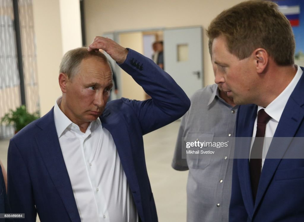 Russian President Vladimir Putin (C) listens to Governor of Sevastopol Dmitry Ovsyannikov (R) while visiting a newly opened school on August 18, 2017 on Sevastopol, Crimea. Vladimir Putin is in a three day trip to the Black Sea city of Sevastopol, located in Crimean Peninsula, a disputed territory between Ukraine and Russia, annexed in 2014. Photo by Mikhail Svetlov/Getty Images)