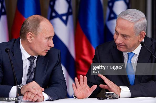 Russian President Vladimir Putin listens to Israeli Prime Minister Benjamin Netanyahu as they prepare to deliver joint statements after their meeting...