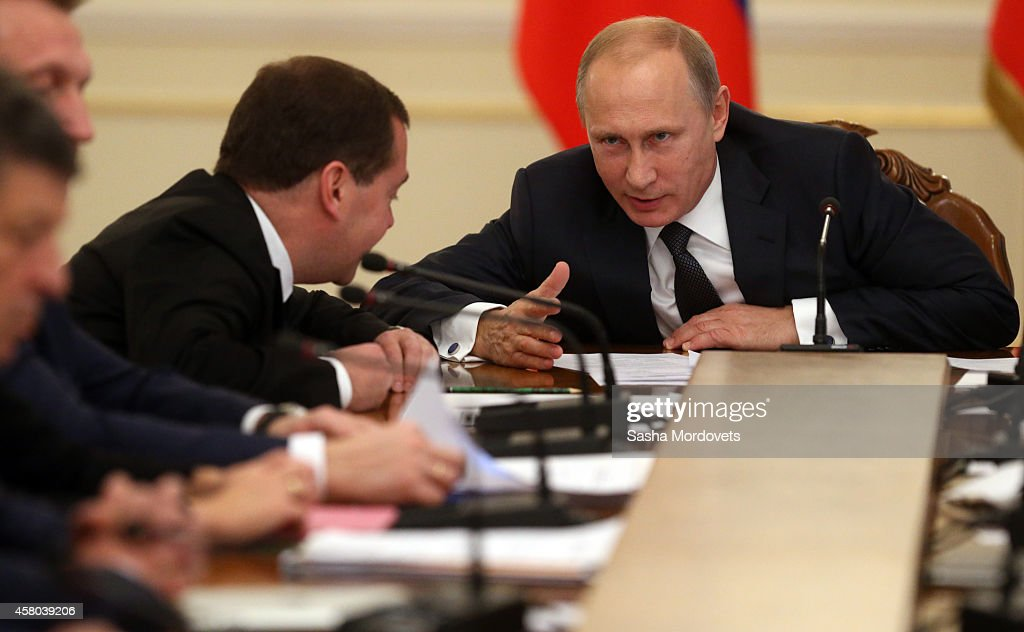 Russian President Vladimir Putin (R) listens to Prime Minister Dmitry Medvedev during a weekly meeting with ministers of the government at the Novo Ogaryovo state residence October 29, 2014 in Moscow Russia.