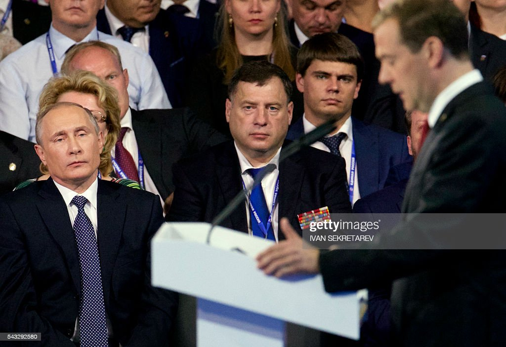 Russian President Vladimir Putin (L) listens to the speech of Prime Minister Dmitry Medvedev, during the 15th Convention of the ruling party United Russia in Moscow on June 27, 2016, ahead of parliamentary elections in September. / AFP / POOL / Ivan Sekretarev