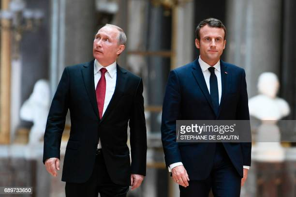 Russian President Vladimir Putin looks around in the Galerie des Batailles as he arrives with French President Emmanuel Macron for a joint press...
