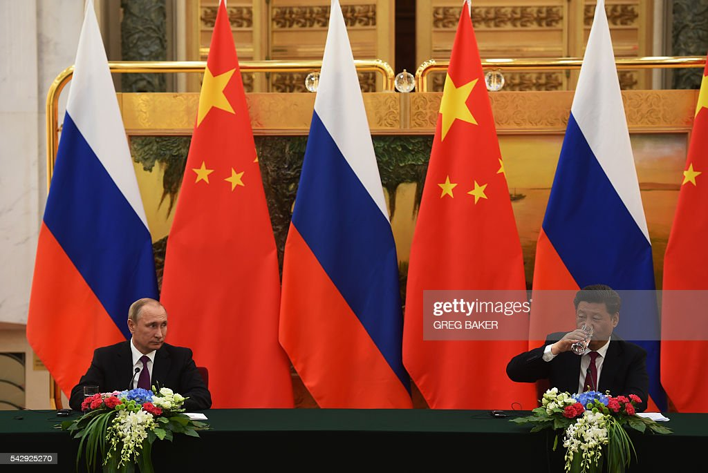 Russian President Vladimir Putin (L) looks at Chinese President Xi Jinping during a joint press briefing in Beijing's Great Hall of the People on June 25, 2016. / AFP / POOL / GREG