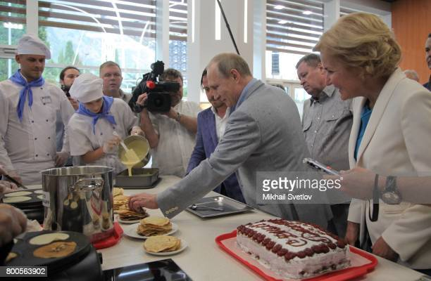 Russian President Vladimir Putin looks at food being prepared at Artek camp an international children center on the Black Sea on June 24 2017 in...