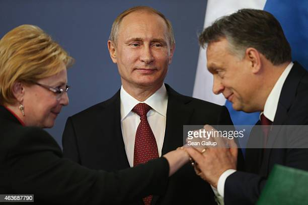 Russian President Vladimir Putin looks on as Hungarian Prime Minister Viktor Orban kisses the hand of a member of the Russian delegation during a...