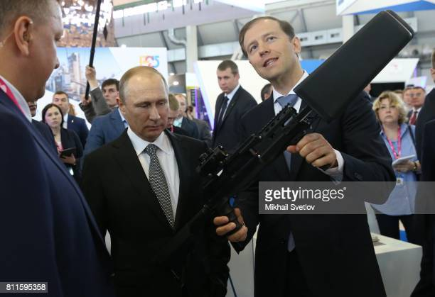 Russian President Vladimir Putin looks on as Industry and Trade Minister Denis Manturov holds an antidrone gun while visiting the Innoprom exhibition...