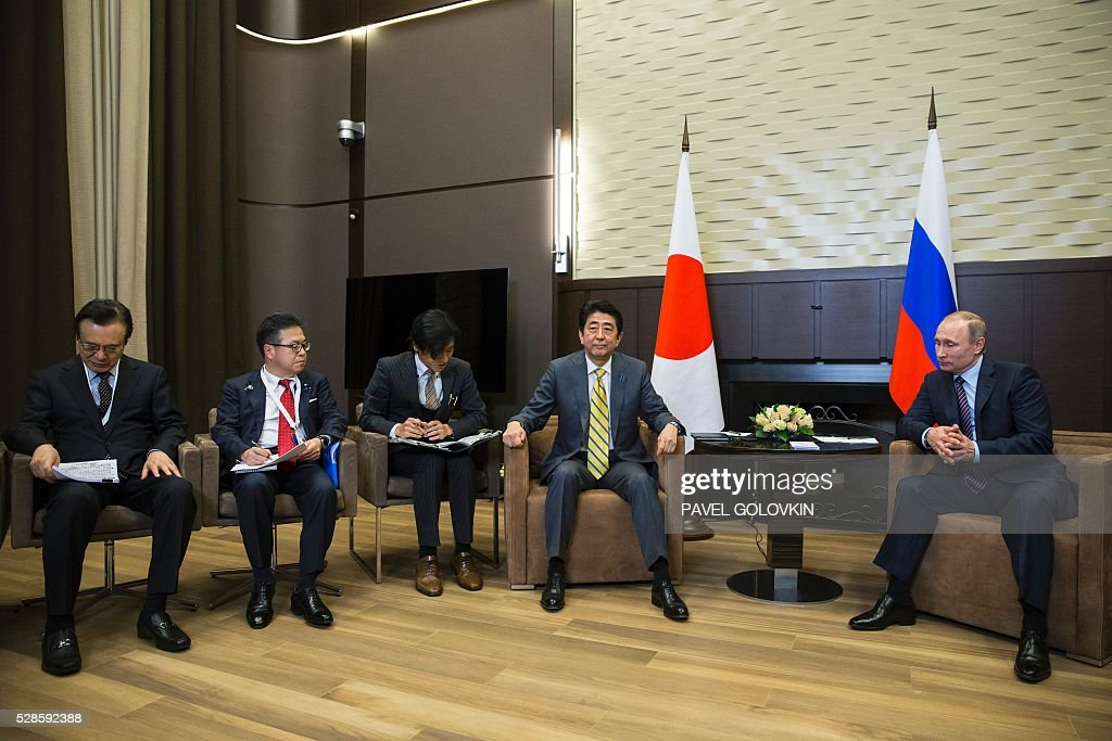 Russian President Vladimir Putin (R) meets with Japanese Prime Minister Shinzo Abe (C) at the Bocharov Ruchei state residence in Sochi on May 6, 2016. / AFP / POOL / Pavel Golovkin