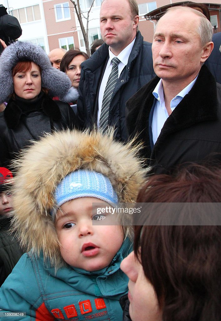 Russian President Vladimir Putin (R) meets with residents during a visit to the town of Krymsk in the southern Russian Krasnodar region on January 11, 2013. The country's worst flooding disaster of recent history killed at least 171 people while nearly 35,000 people lost part or all of their belongings in the flooding on July 7, 2012.