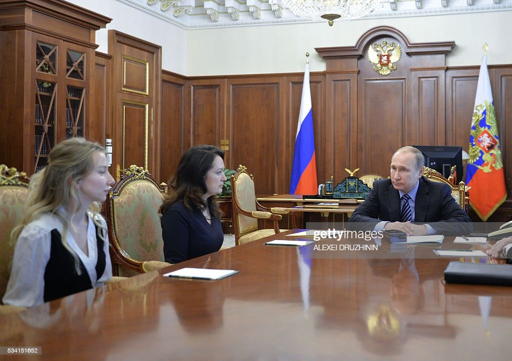 Russian President Vladimir Putin (R) meets with Yekaterina Kornelyuk (C) and Marianna Voloshina (L), the relatives of two Russian journalists killed in eastern Ukraine in June 2014, at the Kremlin in Moscow on May 25, 2016. Russian President Vladimir Putin on Wednesday said the relatives of two Russian journalists killed in eastern Ukraine had asked him to pardon Ukrainian pilot Nadiya Savchenko, convicted of complicity in their deaths. / AFP / SPUTNIK / ALEXEI