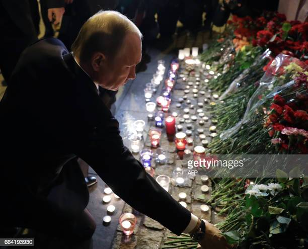 TOPSHOT CORRECTION Russian President Vladimir Putin places flowers in memory of victims of the blast in the Saint Petersburg metro at Technological...