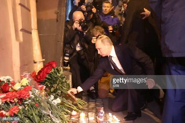 TOPSHOT Russian President Vladimir Putin places flowers in memory of victims of the blast in the Saint Petersburg metro outside Technological...