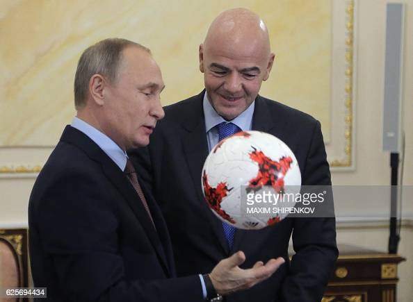 Russian President Vladimir Putin plays with an official match ball for the 2017 FIFA Confederations Cup named 'Krasava' as he meets with FIFA...