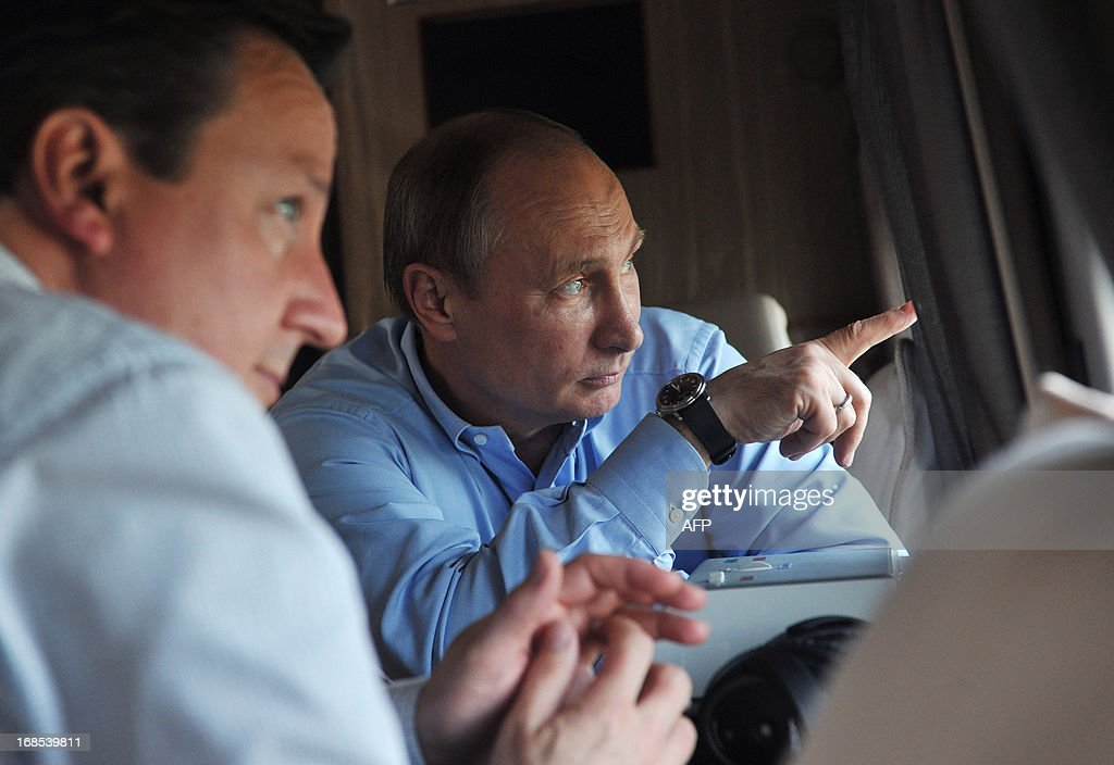 Russian President Vladimir Putin (R) points out the window as he and Britain's Prime Minister David Cameron fly by helicopter to inspect the 2014 Winter Olympic facilities after their meeting at the Bocharov Ruchei state residence in Sochi on May 10, 2013. Britain and Russia on May 10 sought to forge a joint approach to the crisis in Syria, as US Secretary of State John Kerry said there was 'strong evidence' Damascus had used chemical weapons against rebels.