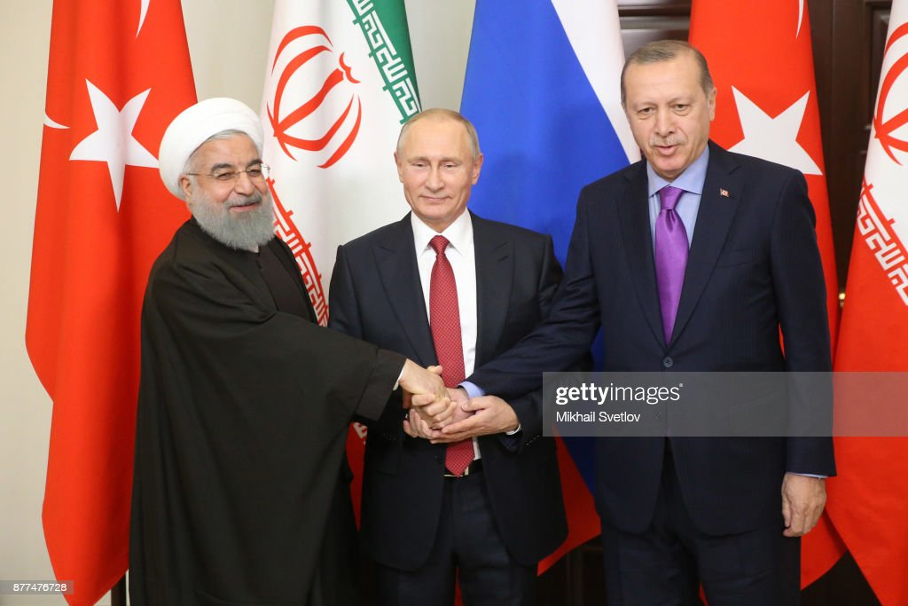 Russian President Vladimir Putin (C) pose for a photo with Turkish President Recep Tayyip Erdogan (R) and Iranian President Hassan Rouhani prior to their talks at Black Sea resort state residence of Bocharov ruchey on November 22, 2017 in Sochi, Russia. Presidents of Russia, Turkey and Iran have gathered in Sochi to talk on Syrian war conflict.