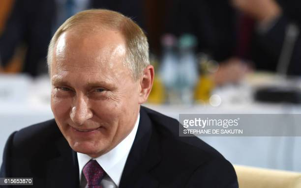 Russian President Vladimir Putin poses ahead of a meeting at the chancellery on October 19 2016 in Berlin German Chancellor Angela Merkel hosts the...