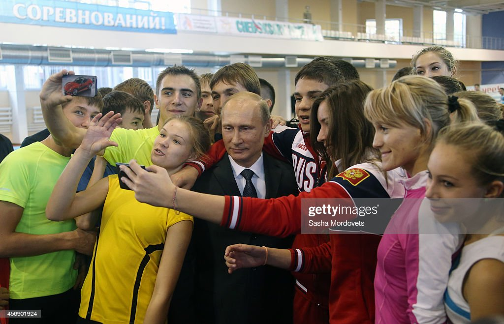 Russian President Vladimir Putin poses for a photo surrounded by teenage athletes as he attends a meeting with officials ministers and governors on...