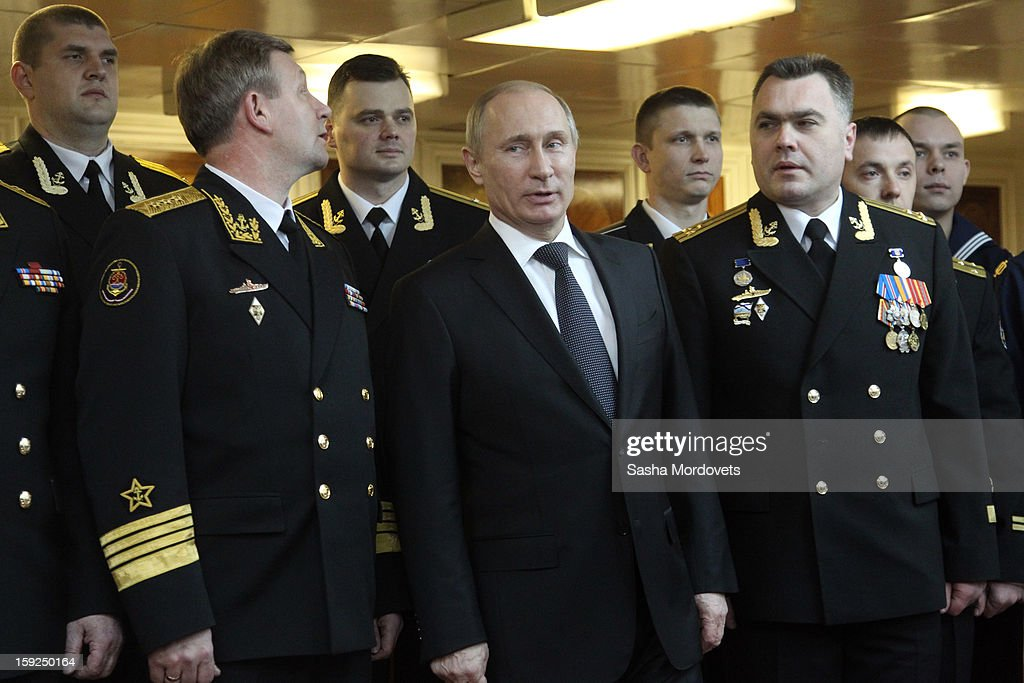 Russian President Vladimir Putin (C) poses for a photo with officers during his visit to the heavy nuclear-powered missile cruiser Pyotr Veliky at the Russian Northern Fleet's base January 10, 2013 in Severomorsk, Russia. Putin awarded the crew of the Pyotr Veliky the Nakhimov order.