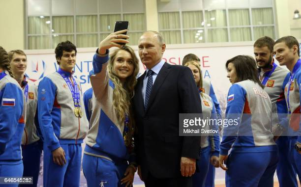 Russian President Vladimir Putin poses for a photo with Russian young athlets winners of the Winter Universiade 2016 on March 1 2017 in Krasnoyarsk...